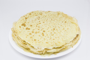 Fried crepes (pancakes) in white plate on white background