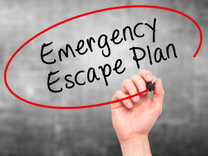 Man Hand writing Emergency Escape Plan with black marker on visual screen. Business, technology, internet concept.