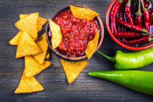 Salsa with tortilla chips and chilli peppers.