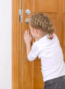 Cute little girl opening door to someone.